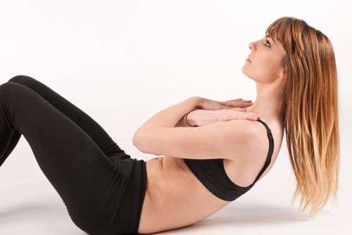 Red-headed girl in black sports bra and pants doing a sit-up on a white background